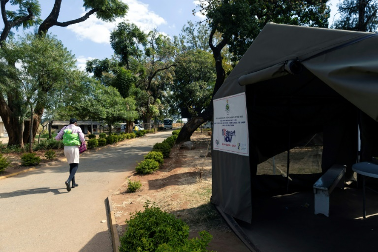 A patient walks past an HIV testing tent in Harare, Zimbabwe in June 2019.