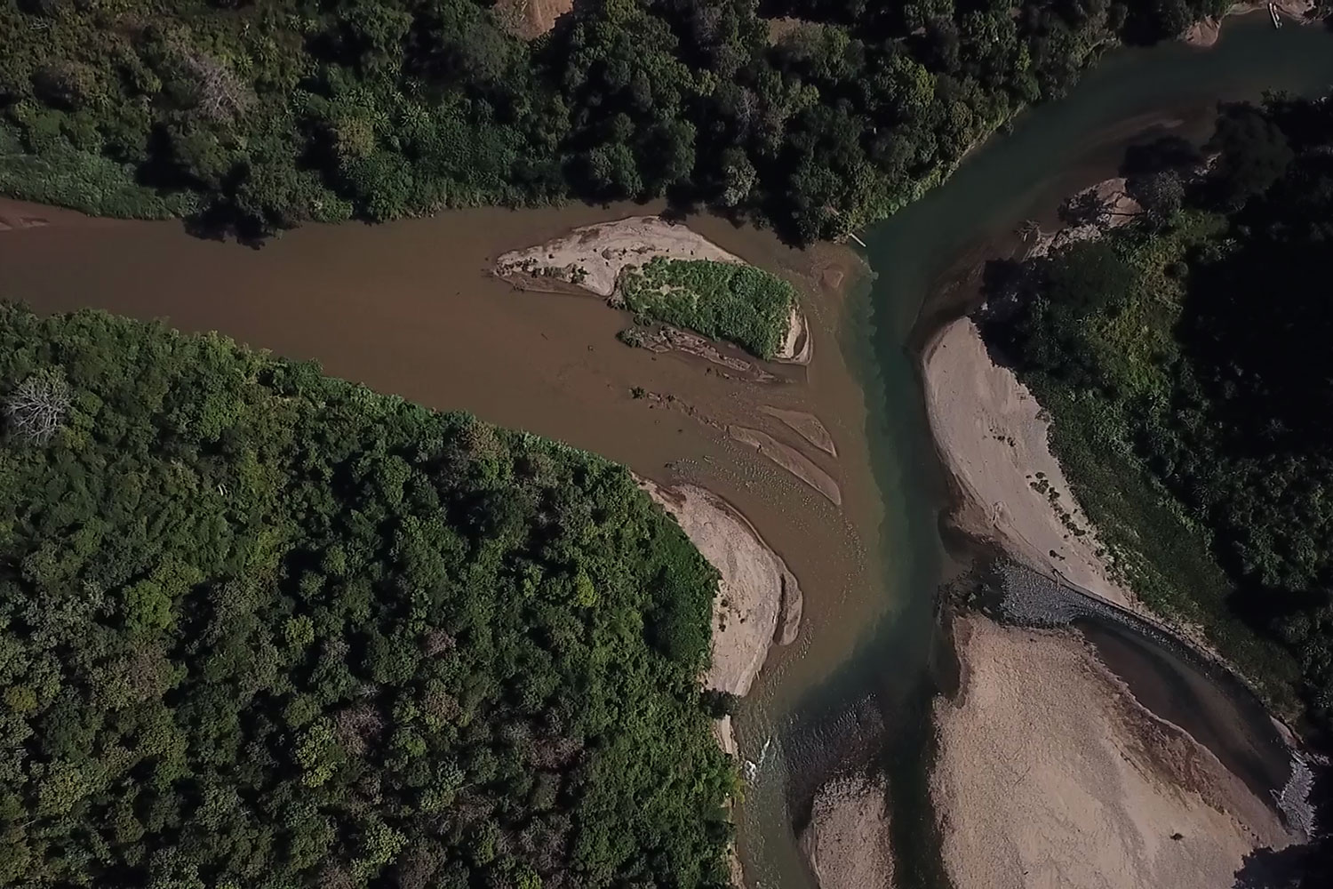 An aerial photo shows the meeting point between the Ngao River and the Yuam River, locally known as the two-coloured river. The area has been included as part of the Yuam Water Diversion Project, a scheme to increase the water supply in Bhumibol dam.(Photo: Transbordernews)