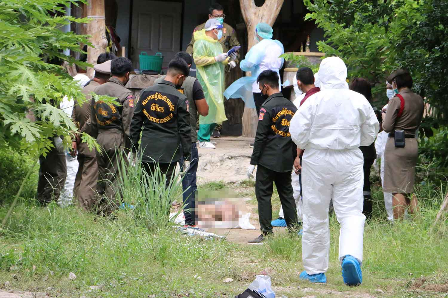 Police inspect the shooting scene at a house in Phichit as rescue workers prepare to take the bodies of people shot dead by a prison official on Wednesday. (Photo: Sitthipoj Kebui)