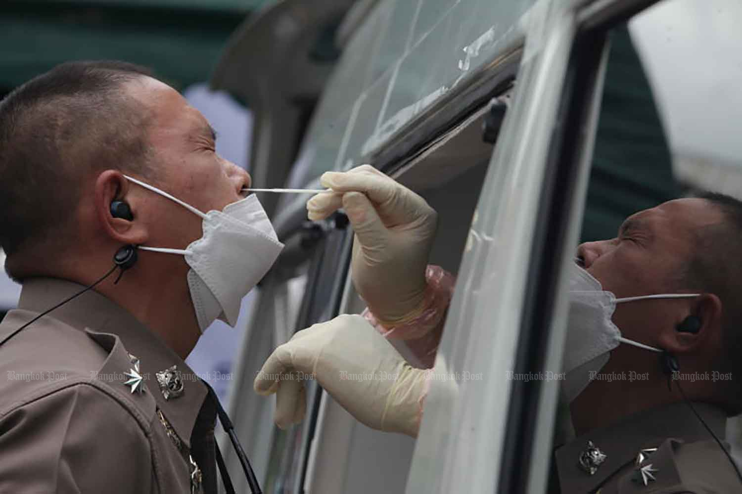 A policeman undergoes a Covid-19 antigen test in the compound of Phlap Phla Chai 1 and 2 police stations in Samphanthawong district, Bangkok, on Friday. (Photo: Apichart Jinakul)