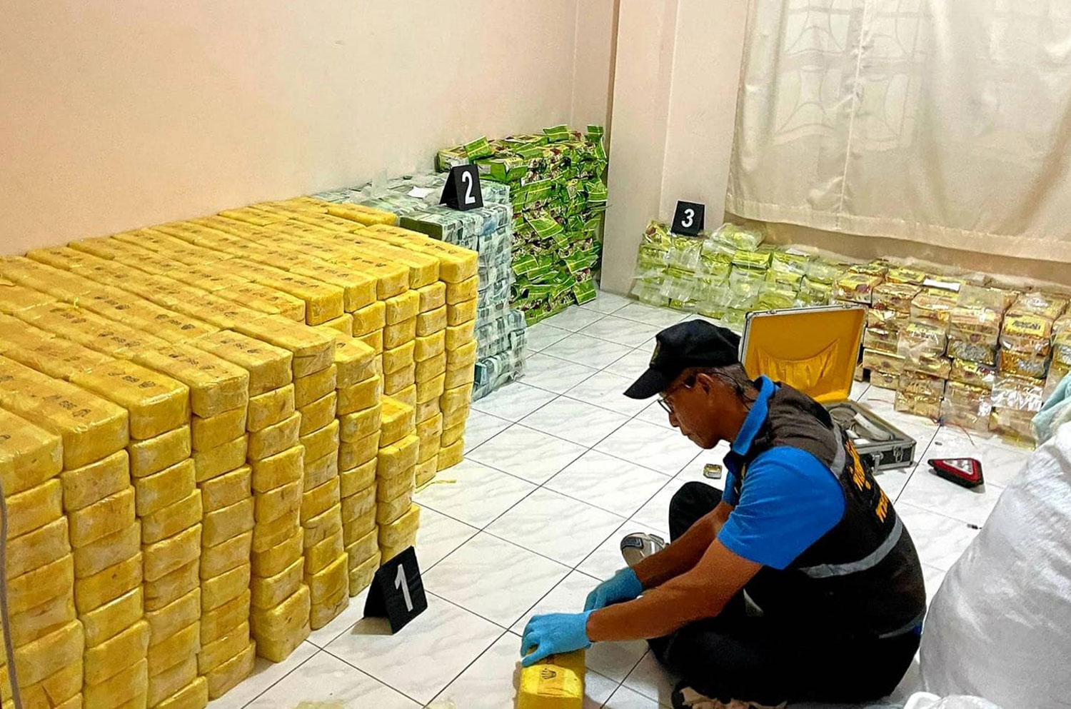 A Narcotics Suppression Bureau officer examines a package of speed pills following a raid on a house in Bang Pa-in district of Ayutthaya on Friday night where over 7 million speed pills and other drugs were seized and seven people caught. (Photo: Sunthorn Pongpao)