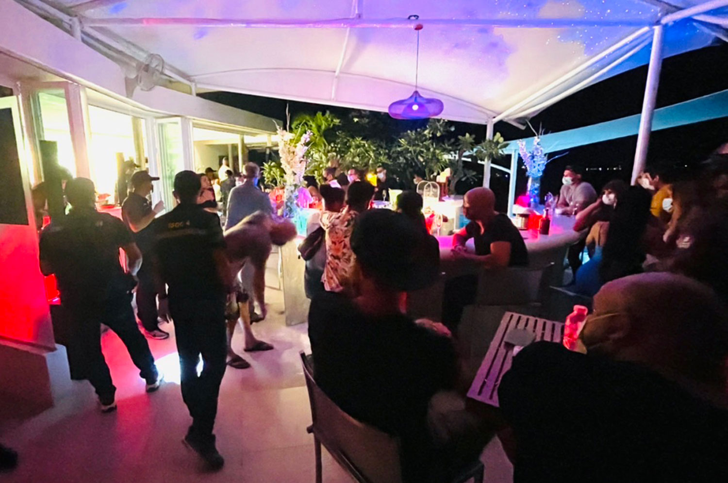 Police, soldiers and local officials round up guests at a birthday party held in violation of Covid restrictions at a Koh Samui resort early Saturday. (Photo: Koh Samui Covid-19 operation centre)