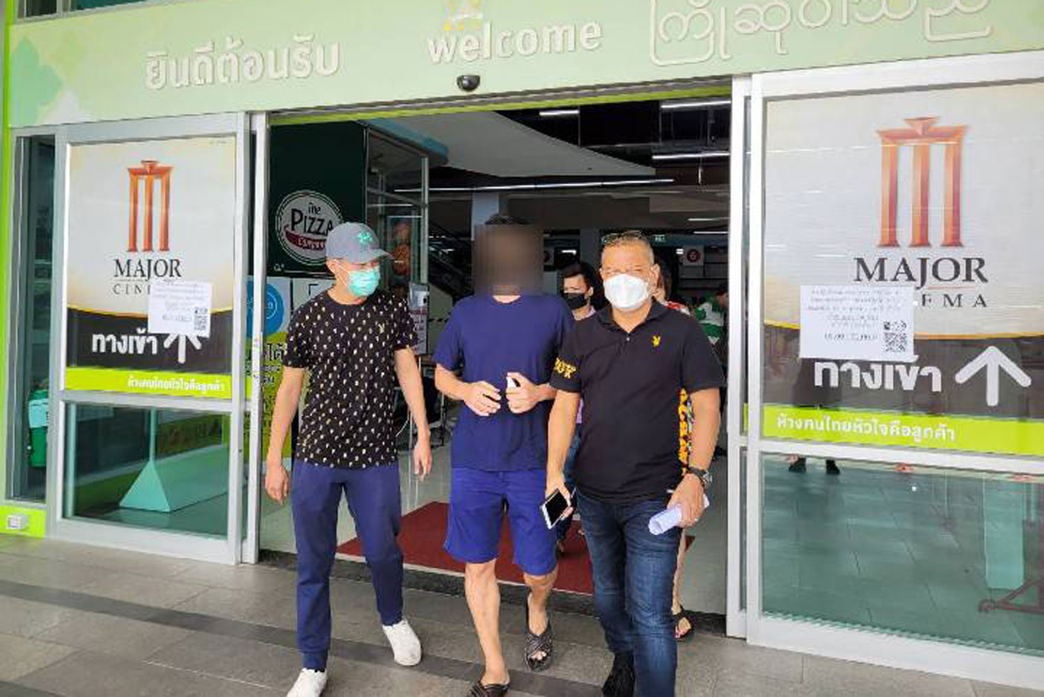 Plainclothes police escort a fugitive boat captain accused of abusing Cambodian workers from a department store in Samut Sakhon on Saturday. (Photo supplied by Anti-Trafficking in Persons Division)