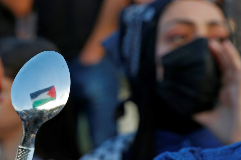 Arab-Israeli protesters lift spoons, reportedly the digging tool used by six Palestinians who escaped from Israel's Gilboa prison, as they demonstrate in the city of Umm al-Fahm in northern Israel on September 10, 2021