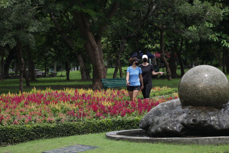 Two women take a stroll through Lumpini Park, normally one of Bangkok's most popular, following the easing of Covid-19 restrictions. (Photo: Apichart Jinakul)