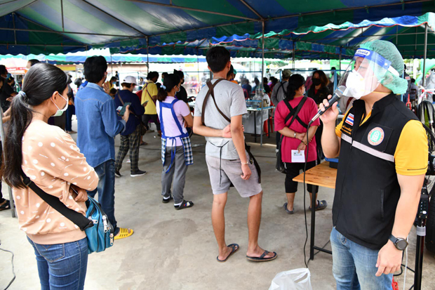 Health officials direct traders waiting to undergo Covid-19 testing at Talad Suranaree on Sunday after 79 who worked at the Nakhon Ratchasima market tested positive for the coronavirus. (Photo: Prasit Tangprasert)