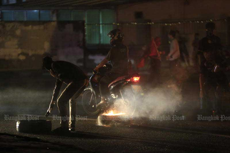 Anti-government protesters watch as fireworks are thrown at police at a demonstration in Din Daeng on Sunday. (AFP photo)