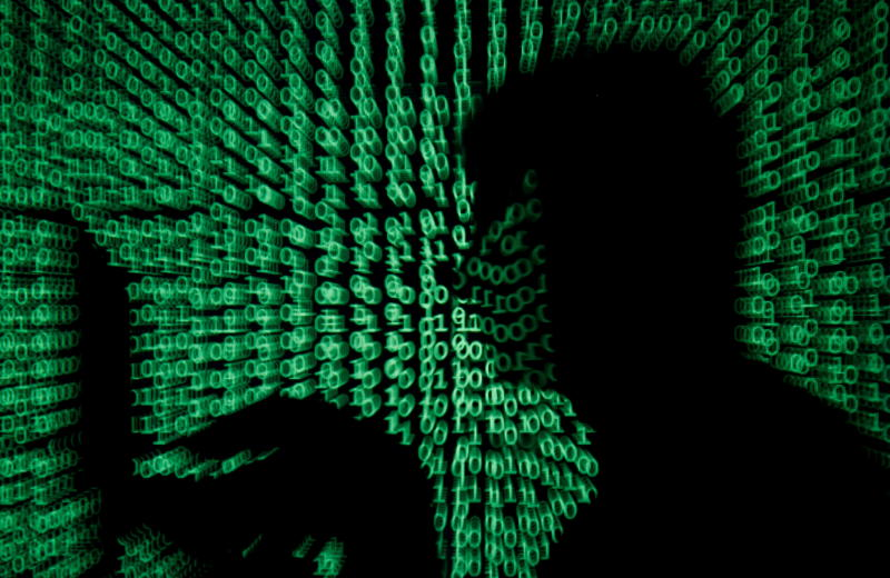 A man holds a laptop computer as cyber code is projected on him in this illustration picture. (Reuters file photo)