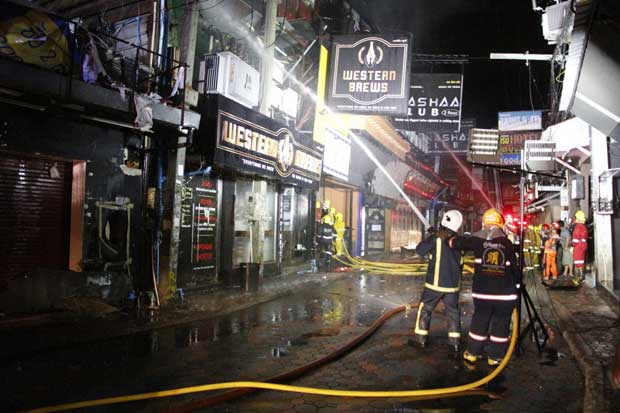 Firefighters continue to spray water on the burned out Club Nashaa building after  bringing the blaze in Pattaya's Walking Street under control early on Monday morning. (Photo: Chaiyot Pupattanapong)