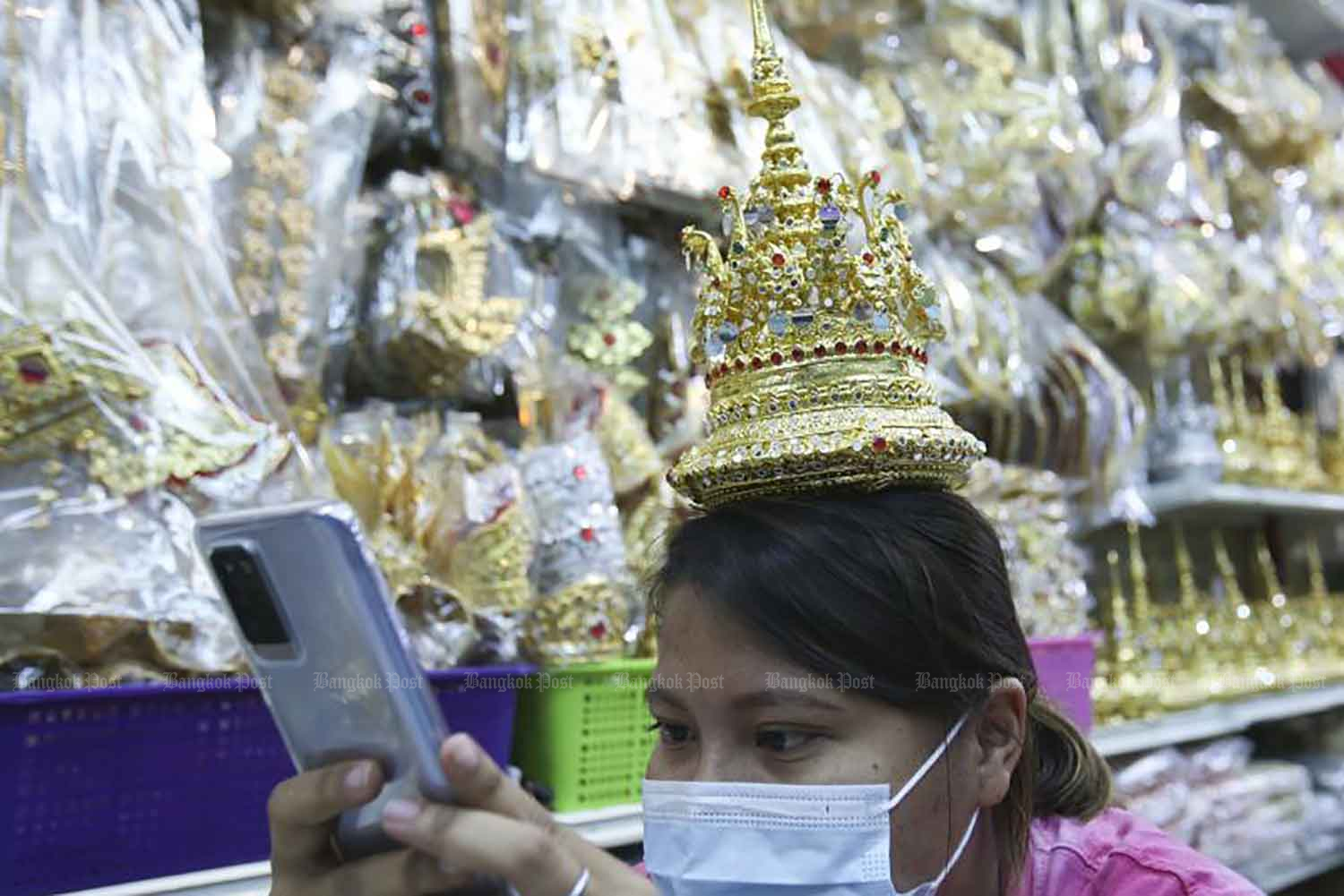 A woman looks at herself wearing 'rad klao' headgear while shopping in the Sam Peng area of Bangkok on Monday. Replicas of the headgear - similar to that featured by Thai-born K-pop singer Lalisa 'Lisa' Manoban of the girl group Blackpink, in her latest music video sensation - are selling like hot cakes. (Photo: Pattarapong Chatpattarasill)