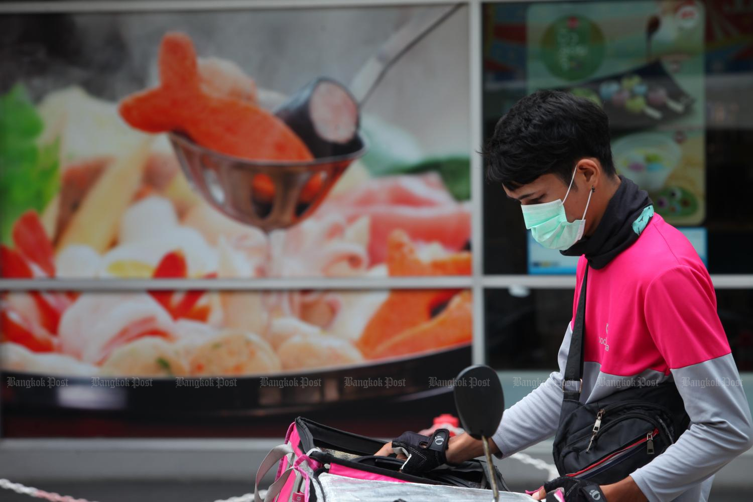 A food delivery rider sets off after receiving an order.Photo by Apichart Jinakul.