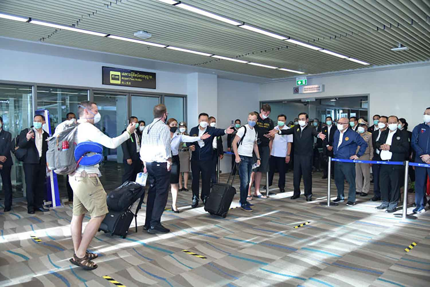 Prime Minister Prayut Chan-o-cha and his delegation welcome the first foreign tourists to arrive at Phuket International Airport when the sandboxed province reopened on July 1. (Government House photo)