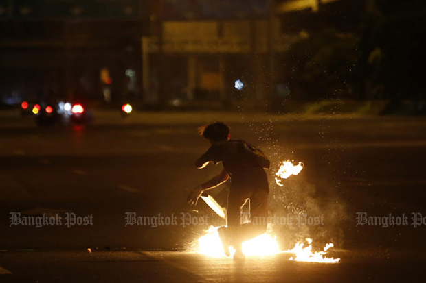 An anti-goverment protester lights a fire during a clash with riot police in Din Daeng area on Tuesday. (Photo: Wichan Charoenkiatpakul)
