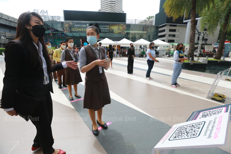 Employees of shops at Siam Paragon queue for a temperature check when returning from lunch on Wednesday. (Photo: Somchai Poomlard)