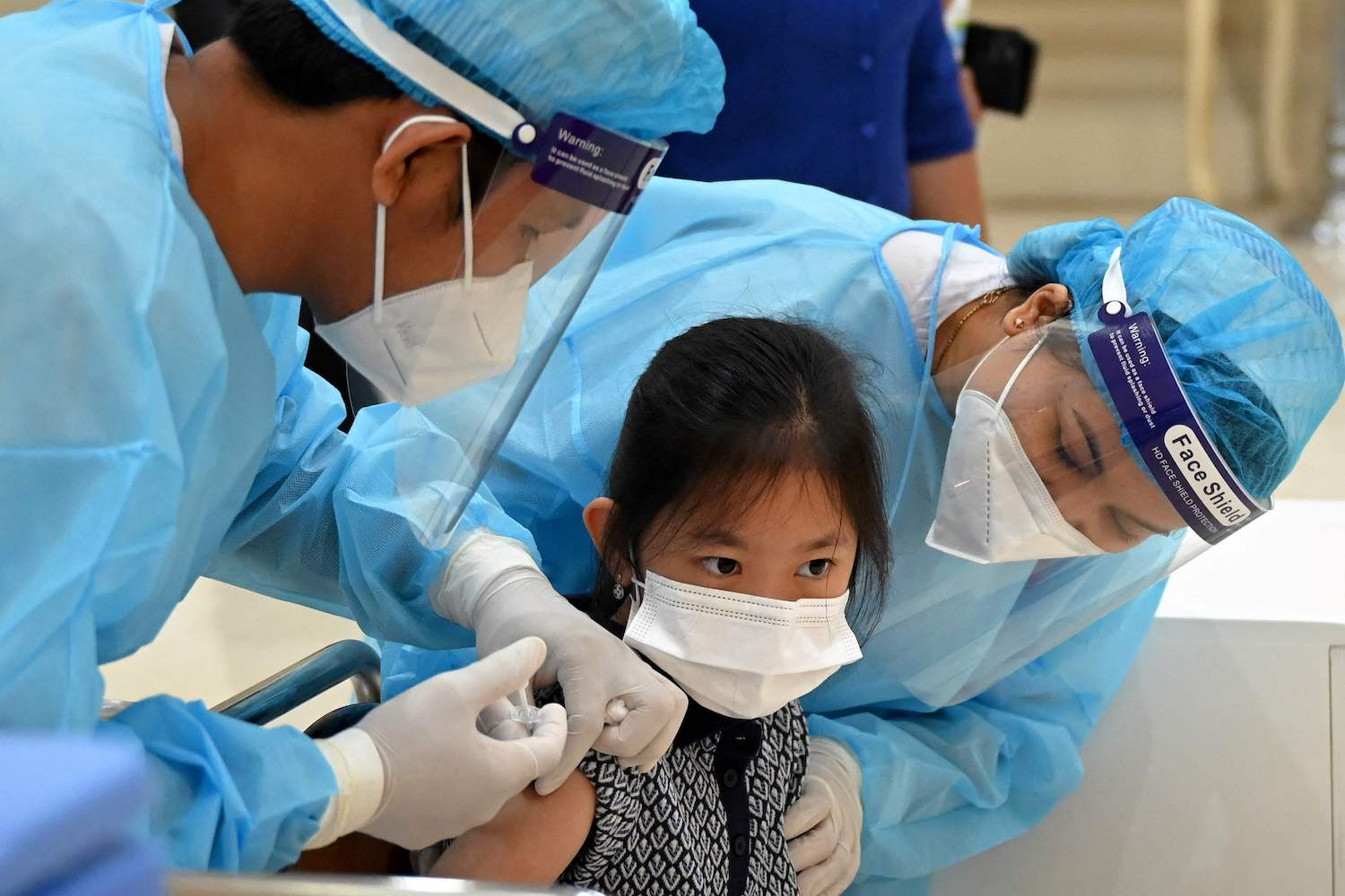 A granddaughter of Prime Minister Hun Sen receives a dose of Sinovac coronavirus vaccine at the Peace Palace in Phnom Penh on Friday, as Cambodia begins vaccinating children aged between six and 12. (AFP Photo)