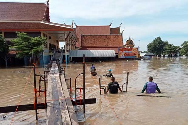 Soldiers build a temporary bridge for monks and worshippers visiting Wat Chula Manee after the temple in Bang Ban district of Ayutthaya province was flooded. (Photo: Sunthong Pongpao)