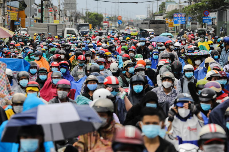 People, mostly migrant workers who are planning to return to their hometowns, wait at a checkpoint to leave Ho Chi Minh City, Vietnam on Friday. (Reuters photo)