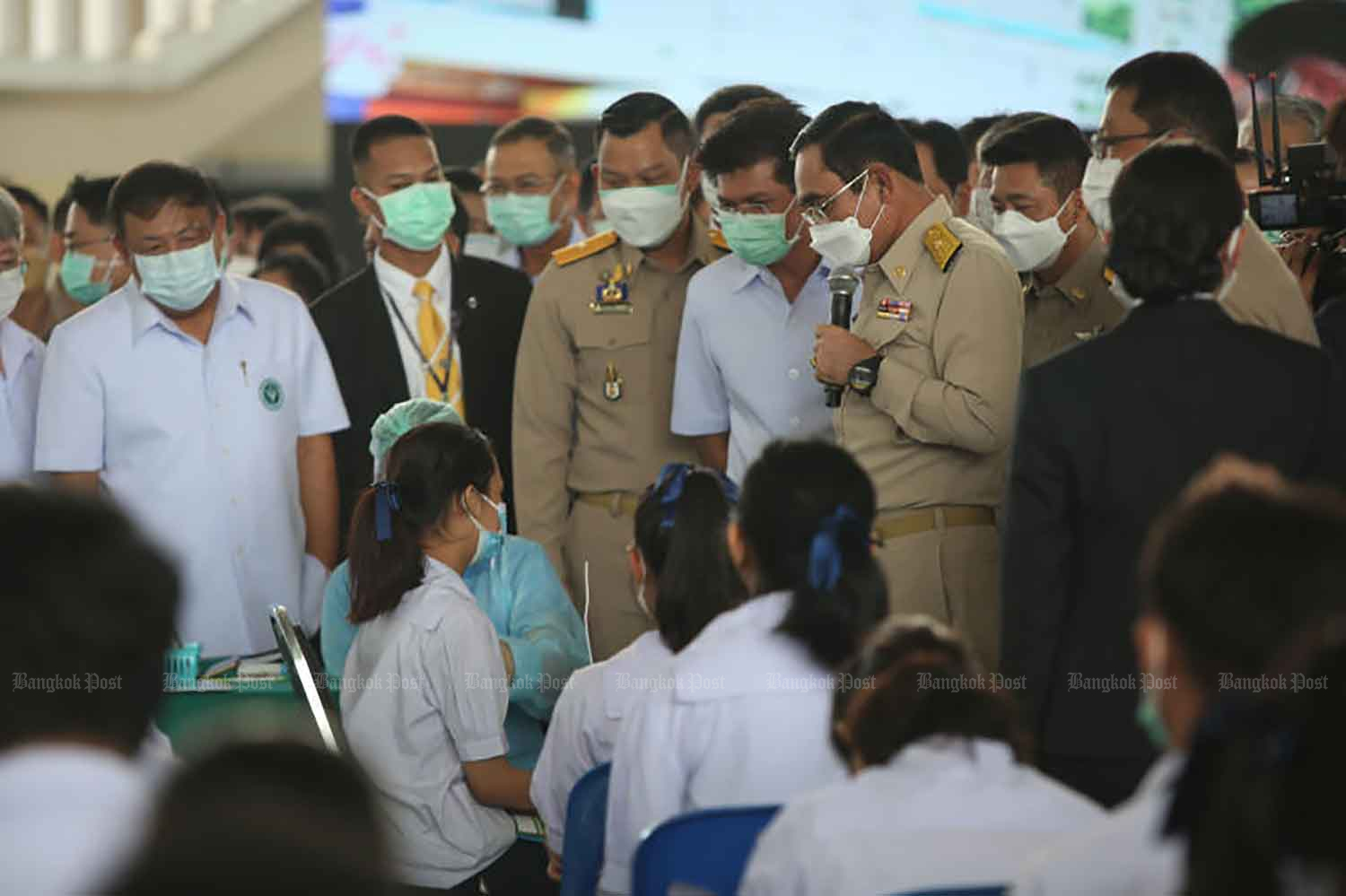 Prime Minister Prayut Chan-o-cha speaks to school children at the Pibool Upphatham School in Bangkok's Lat Phrao district where he presided over the kick-off of the vaccination campaign for young people aged 12-18 on Monday. The jabs are offered so on-site learning can resume in the new term next month. (Photo: Varuth Hirunyatheb)