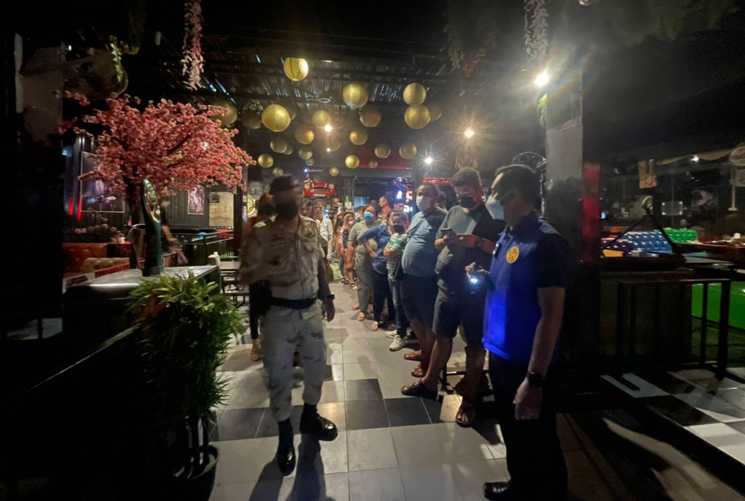 Customers and staff of Lamer Restaurant & Karaoke in Muang district of Nakhon Ratchasima, lined up ready to be taken away after the raid on Wednesday night. (Photo: Rrasit Tangprasert)