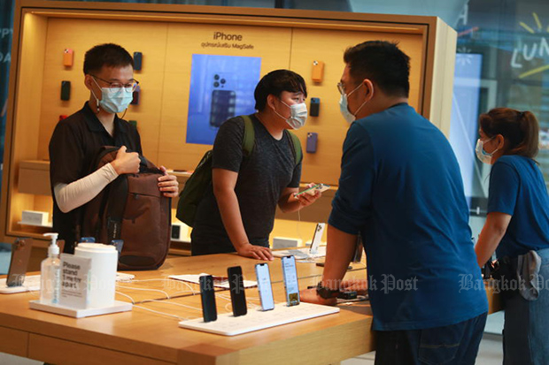 Customers talk to staff at the Apple store at CentralWorld on Friday, the first day of sales of the iPhone 13 series in Thailand. (Photo by Somchai Poomlard)