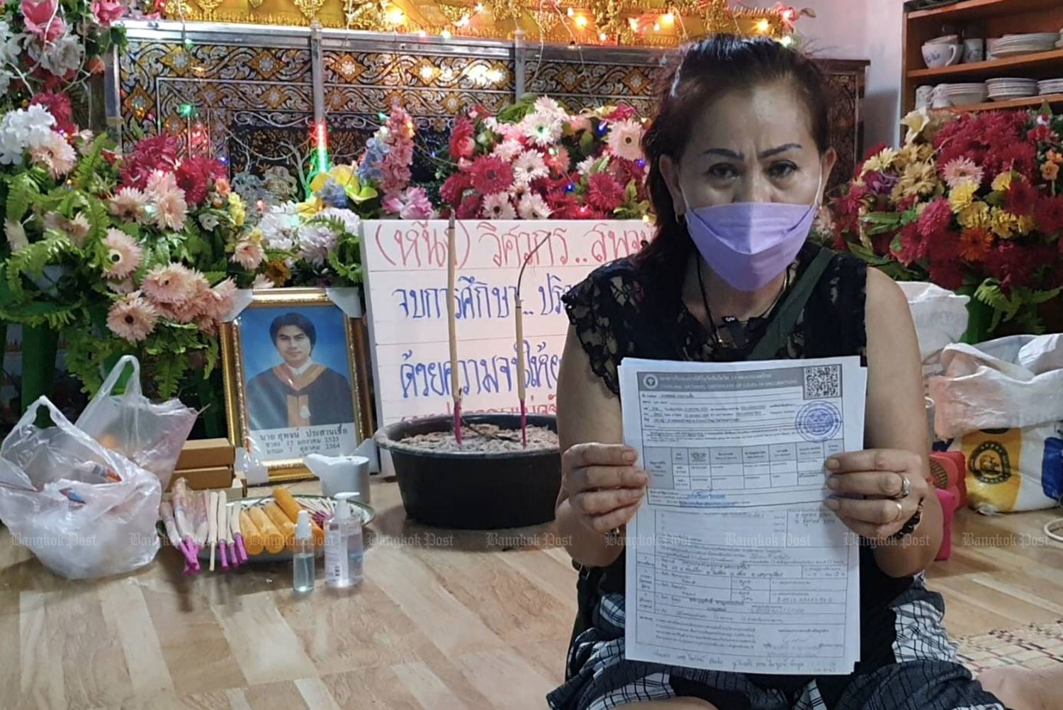 Nattha Nawo shows the vaccination certificate given to her son Supoj Prasarnchue, 39, who died one week after receiving a second dose, of a different Covid-19 vaccine, in Bua Yai district of Nakhon Ratchasima. (Photo supplied: Prasit Tangprasert)