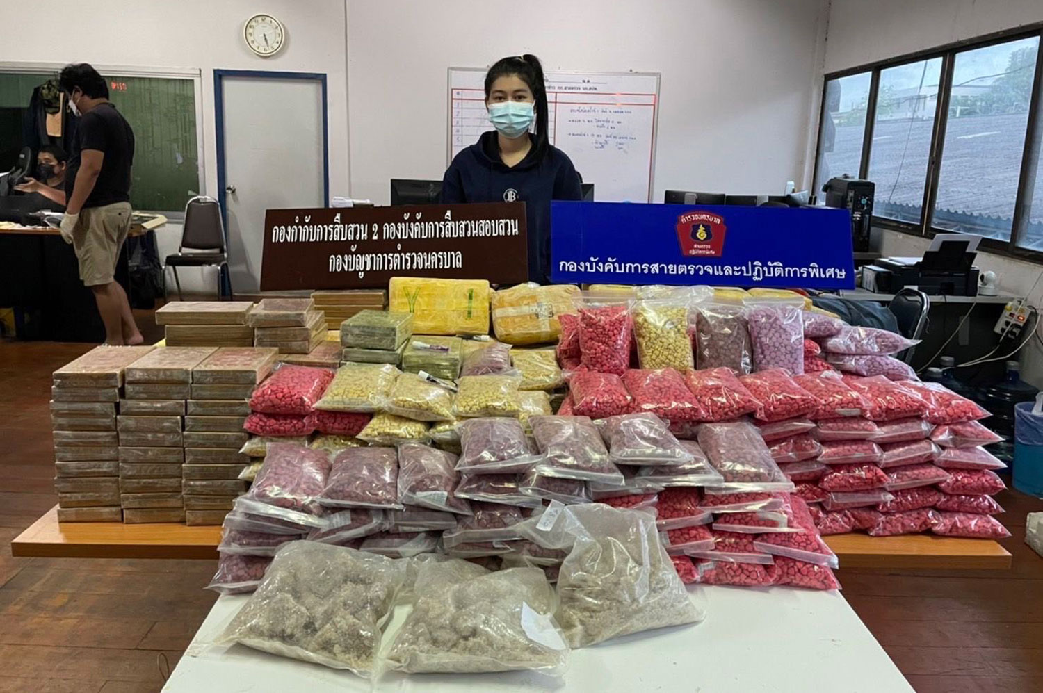 Drug suspect Angkhawipha Karnbanjong, 20, stands behind packages of heroin, methamphetamine, ecstasy pills and crystal meth worth about 157 million baht, seized from one of two vehicles used for drug smuggling.(Photo supplied: Wassayos Ngamkham)