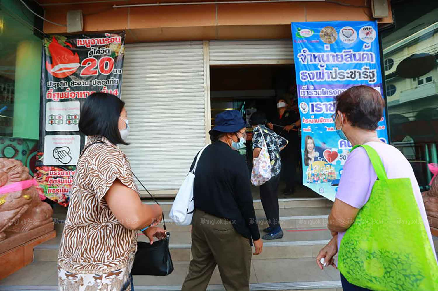Holders of state welfare cards arrive at a store to buy discounted products provided by the government in Samut Prakan province in February. (Photo: Somchai Poomlard)