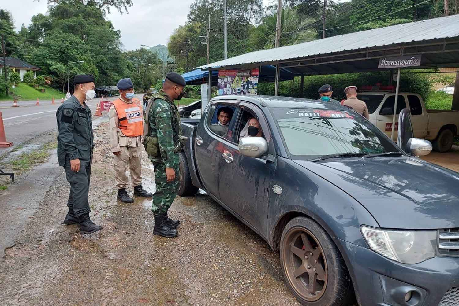 Soldiers search a pick-up truck at a checkpoint in tambon Pang Phle in Kanchanaburi's Sangkhla Buri district on Wednesday morning. Two Thai women were arrested for transporting Myanmar migrants to Three Pagodas border checkpoint, violating the ban against moving migrants to contain the Covid-19 pandemic. (Photo: Piyarat Chongcharoen)