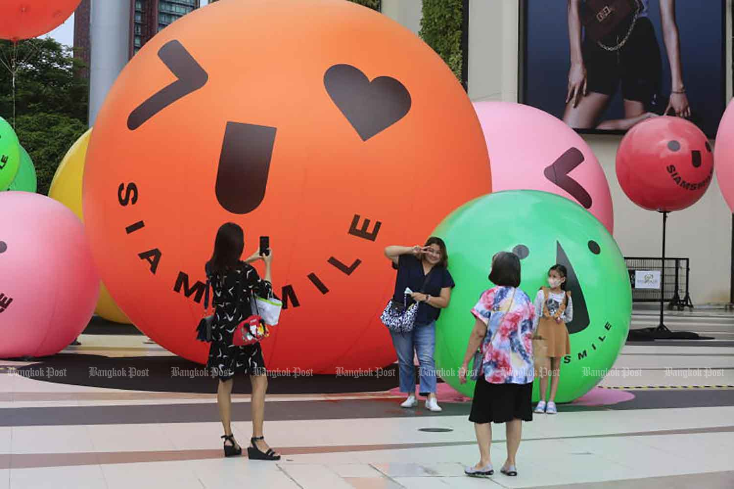 People take photos in front of Siam Paragon shopping centre in Bangkok's Pathumwan district of Bangkok on Tuesday. Officials plan to allow shopping centres and other venues to organise events with at least 50 participants on Saturday. (Photo: Pornprom Satrabhaya)