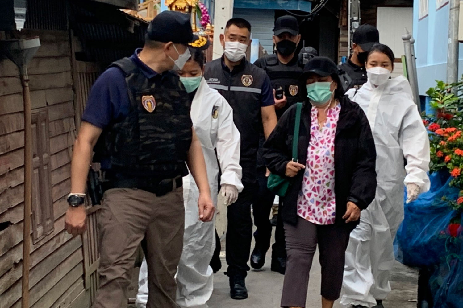 Wassana Meechan, 54, centre right, is arrested in Phra Samut Chedi district on Thursday morning by plainclothes police. She was wanted on an arrest warrant for collusion in human trafficking by procuring women for forced prostitution. (Photo supplied)