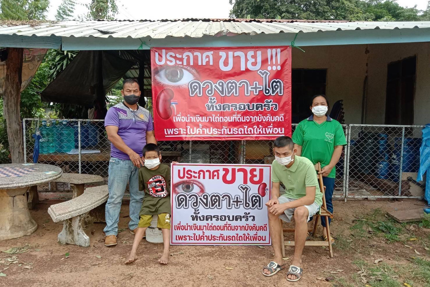 Rakthewa Khapim-udomlarp, 48, of Ubon Ratchathani's Khemarat district, his wife and their two sons, and the signs outside their home offering to sell their eyes and kidneys. (Photo: Good Governance Post Press Agency Facebook page)