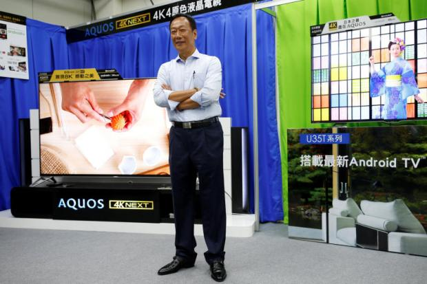Terry Gou, founder of Hon Hai Precision Industry Co Ltd, poses for a photo with Sharp Corp's Aquos TV at a Sharp showroom in New Taipei City yesterday.REUTERS