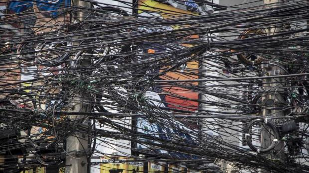 Tangles of power, telecom and other types of cable are a familiar sight in Bangkok and major cities nationwide. The government has vowed to put 127 kilometres of lines underground in three key provinces within five years. (Photo by Thanawat Phetlolian)