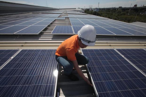 A technician checks out a solar array installed in Samut Prakan. Up to 19 solar farm licences have been revoked after operators failed to start commercial operations as scheduled. Some licence holders had done nothing to begin preparing their solar farms in the run-up to a June deadline. (Photo by Pornprom Satrabhaya)