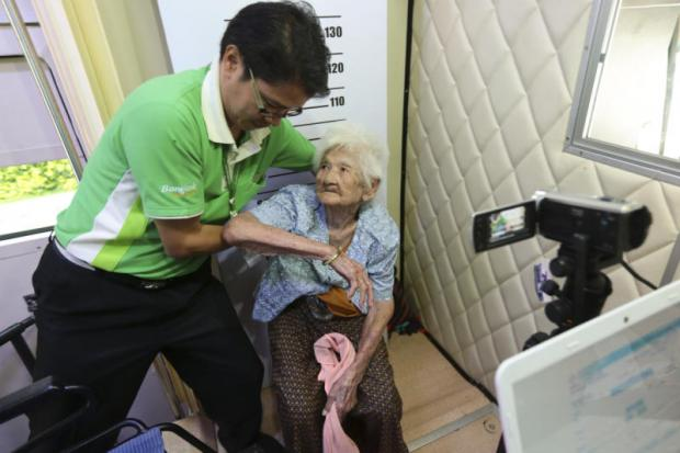 YOU CAN't MAKE ME: A City Hall official assists Nian Pongpichai, 99, as she has her photograph taken for an ID smart card, which the elderly can use in the Aug 7 referendum.