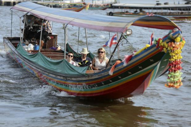 Foreign tourists take a boat ride along the Chao Phraya River. Foreign visitors, who are expected to bring in 1.67 trillion baht to the country this year, are increasingly attracted to domestic agritourism, a type of business in which farmers open their properties to visitors. Patipat Janthong