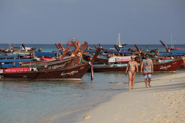 Foreign tourists walk on the beach at Koh Lipe in Satun. The TAT believes Germany is an important market to help Thailand achieve its tourism revenue target of 2.84 trillion baht this year. WICHAN CHAROENKIATPAKUL