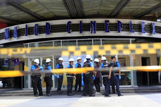 Forensic officials wait outside the fire-gutted Major Cineplex Pinklao building while public work inspectors go inside and determine if it is safe for them to enter and collect evidence.(Photo by Apichart Jinakul)