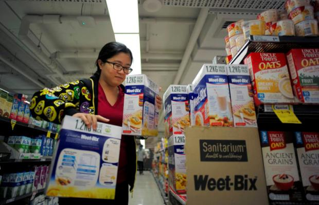 Chinese 'daigou' shopping agent Na Wang selects products during a shopping trip at an Australian supermarket in Sydney.(REUTERS photo)