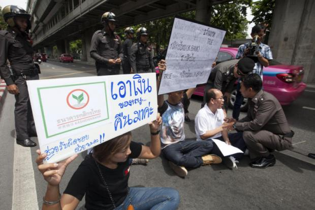 A family from Ayutthaya stages a protest in the middle of Rama 1 Road on Friday calling for police to investigate a banking scam in which the family claims to have lost close to a million baht to an online thief. (Photo by Pawat Laopaisarntaksin)