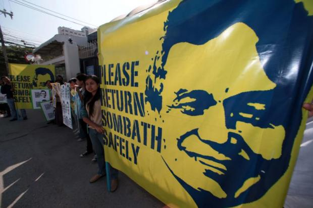 In this photo taken in December 2012, activists hold a large banner featuring a poster of the missing civil society leader Sombath Somphone during a demonstation in Bangkok.Chanat Katanyu