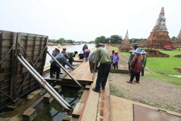 Workers instal temporary flood barriers in front of Wat Chaiwattanaram in Phra Nakhon Si Ayutthaya district of Ayutthaya province following a warning by officials about high water levels in the river caused by discharges from the Chao Phraya dam. (Photo by Sunthorn Pongpao)