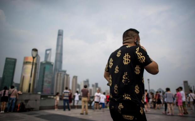 A man walks down the Bund overlooking the financial district of Pudong in Shanghai, China, on July 15. Entrepreneurs are contributing to the growth of megacities, with 10 cities the size of New York coming into being in the developing world every year.AFP
