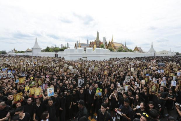 UNITED IN GRIEF: Mourners wave pictures of His Majesty the King before singing the Royal Anthem for the last time at Sanam Luang on Saturday in a mass tribute organised by filmmaker MC Chatrichalerm Yukol. (Photo by Patipat Janthong)