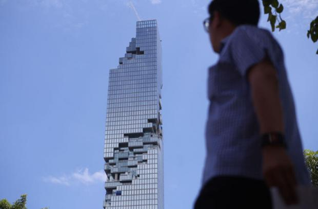 A man walks on Sathon Road with the Mahanakhon building in the background. Economists have suggested Thailand bolster its economy while lessening its reliance on China. JIRAPORN KUHAKAN