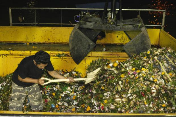 A Bangkok Metropolitan Administration worker uses a shovel to scoop rubbish collected from city waterways following the Loy Krathong festival into a garbage grinder stationed near a pier in Bangkok Noi district on Monday night. Pornprom Satrabhaya