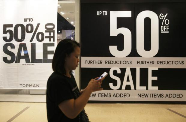 A woman walks past a sign advertising a sale at a Bangkok mall. The World Bank has raised Thailand's GDP forecast to 3.2% next year, up from 3.1%.SEKSAN ROJJANAMETAKUN