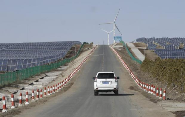 A vehicle drives past solar panels and wind turbines an an energy storage and transmission site operated by State Grid Corporation of China, in Zhangjiakou in Hebei province. (Photo: Reuters)