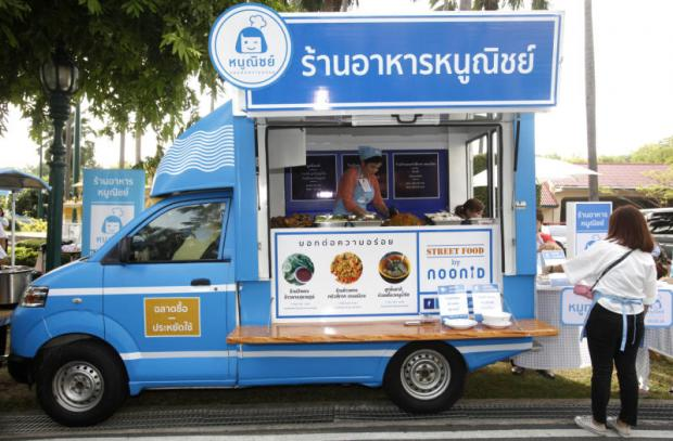 A woman buys food from a mobile unit that operates under the Noo Nid scheme.