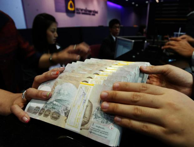 A client deposits money at Siam Commercial Bank. The Bank of Thailand says foreign investors regard Thai assets as a safe haven, giving strength to the baht.PHRAKRIT JUNTAWONG